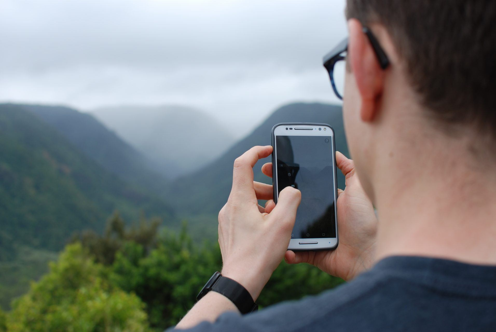 Young man in glasses holding cell phone while hiking,