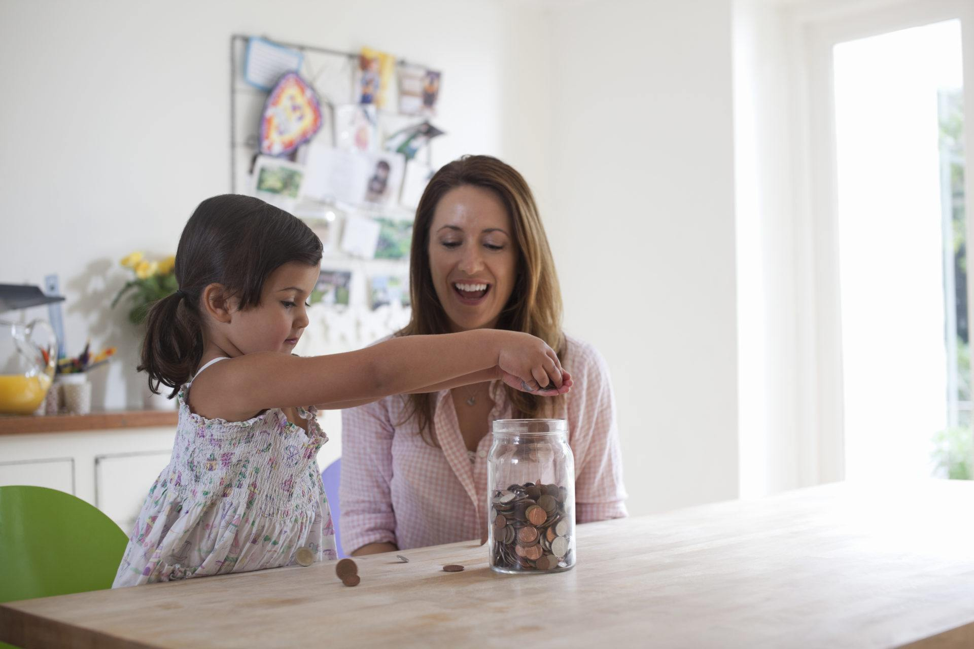 Mother and daughter putting pennies in a jar