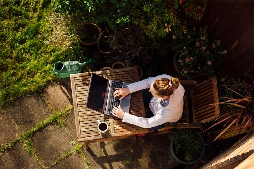 Woman in garden on laptop