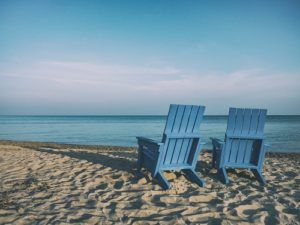 Two Adirondack chairs overlook a calm beach