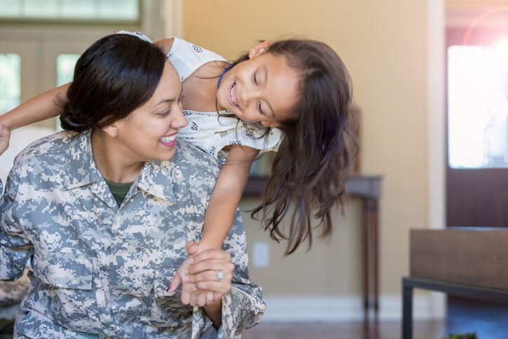 Female soldier playing with daughter