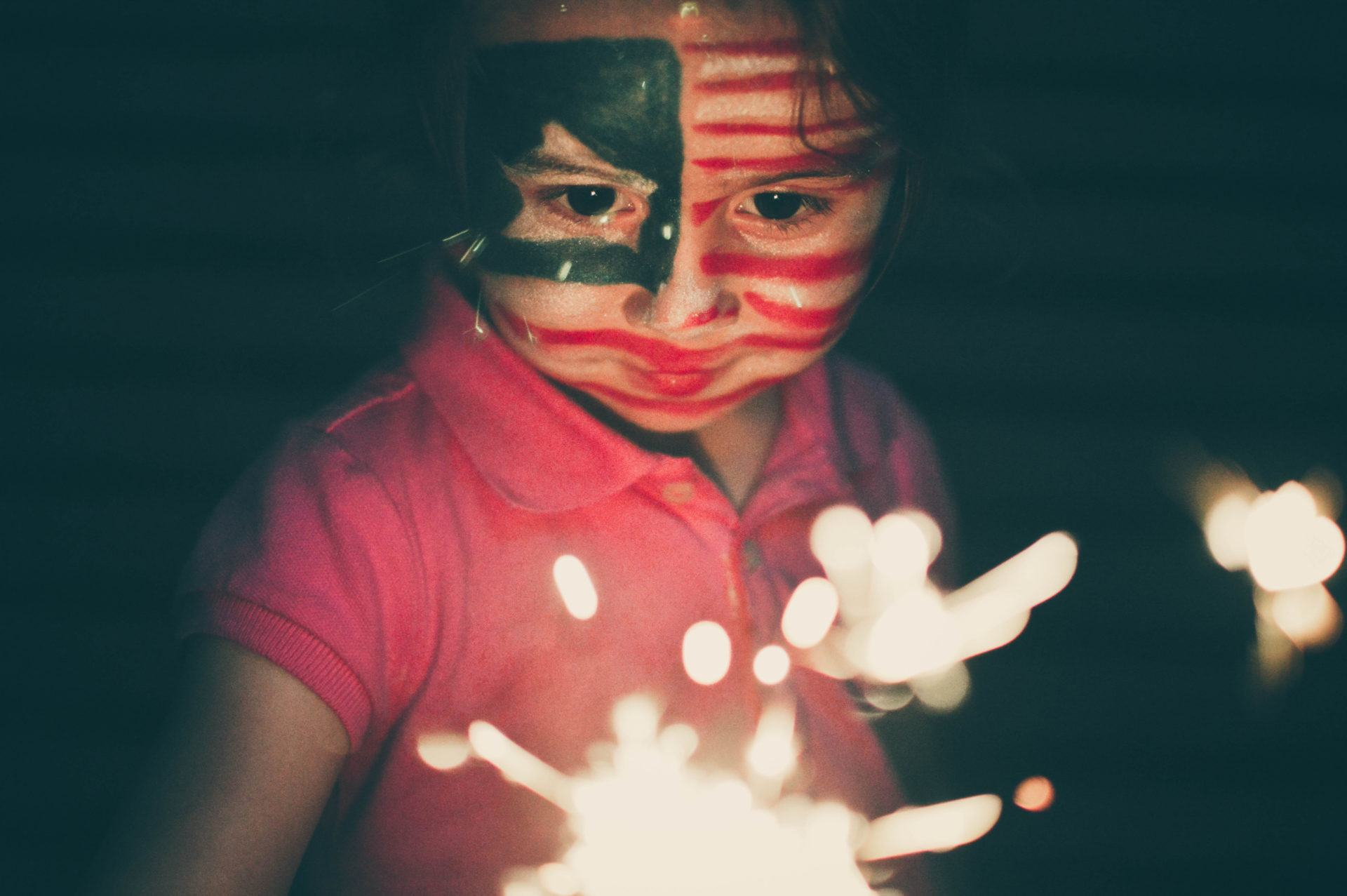 A young girl with her face painted red white and blue and a sparkler in her hand at night outside.
