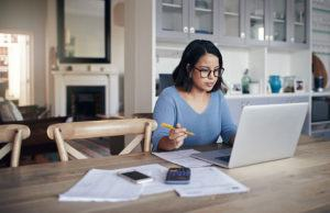 Woman studying at kitchen table on laptop
