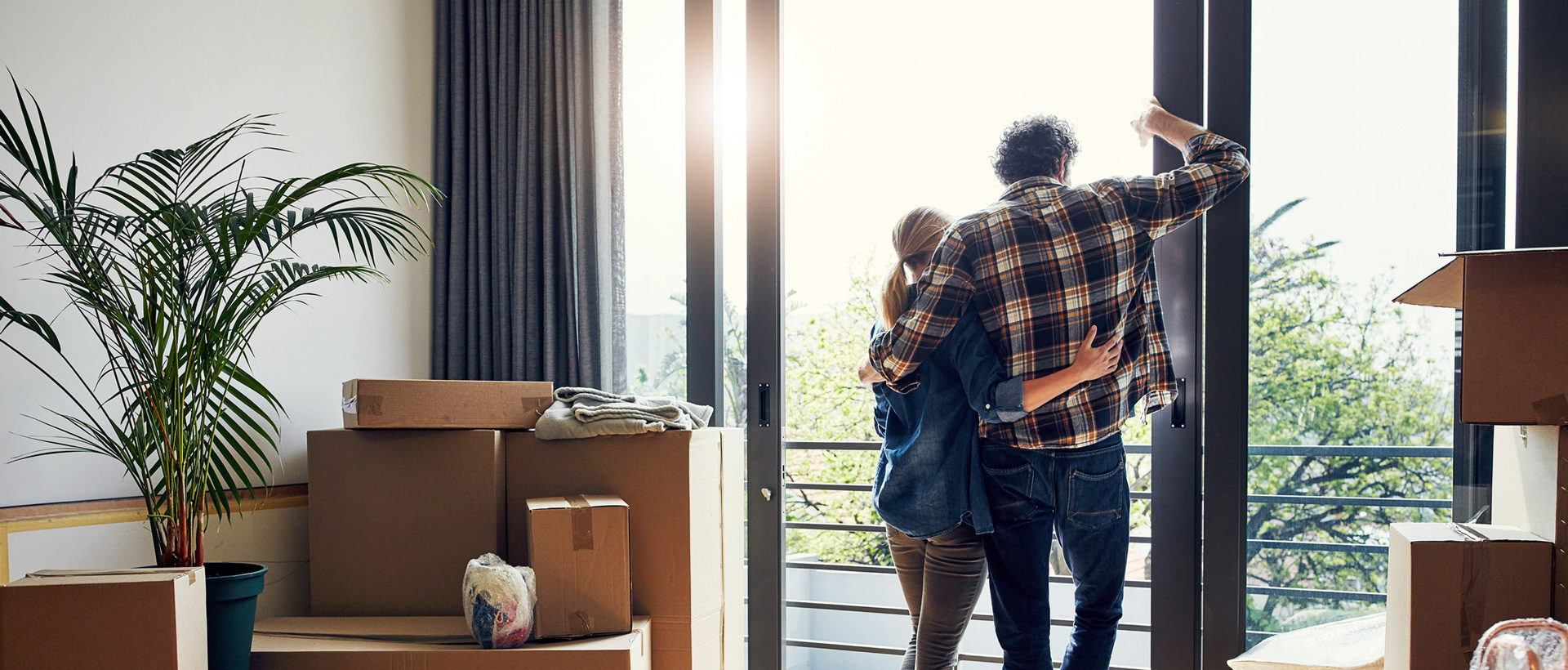 Man and woman embracing in a home with moving boxes