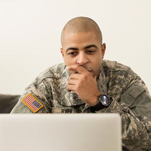 Serviceman looking at a laptop