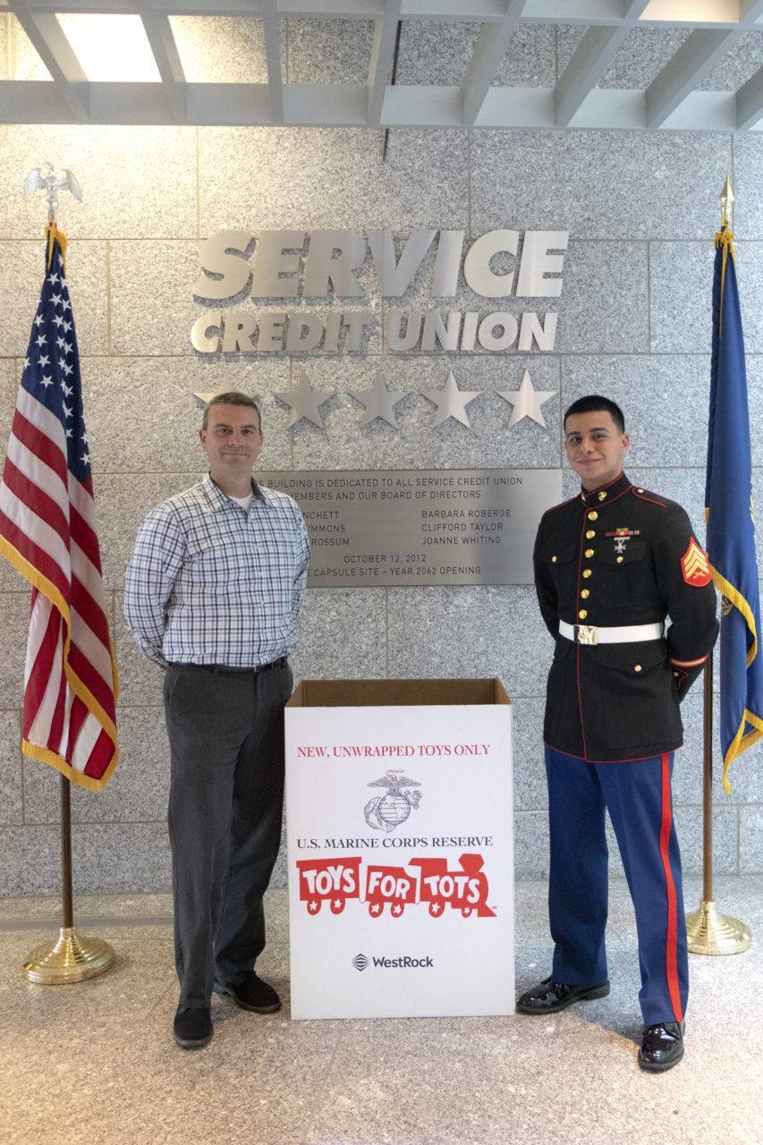 two employees standing next to a Toys for Tots donation box