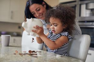Mother and child getting money from a piggy bank