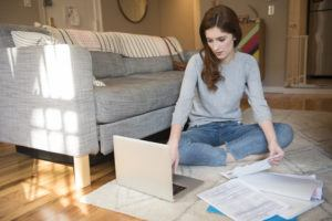 Woman sitting on floor paying bills with laptop