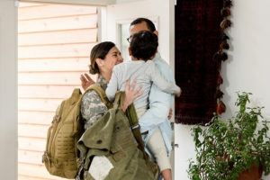 Female soldier hugging family