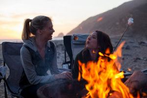 Two girls by camp fire