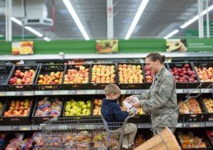 Female soldier shopping in grocery store with son