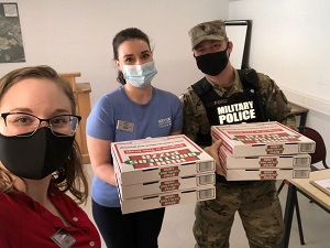 Service CU staff delivering pizza to the MP station
