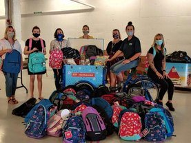 Service CU staff pack backpack donations