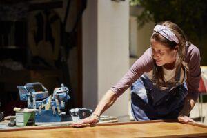 Woman polishing furniture outdoors